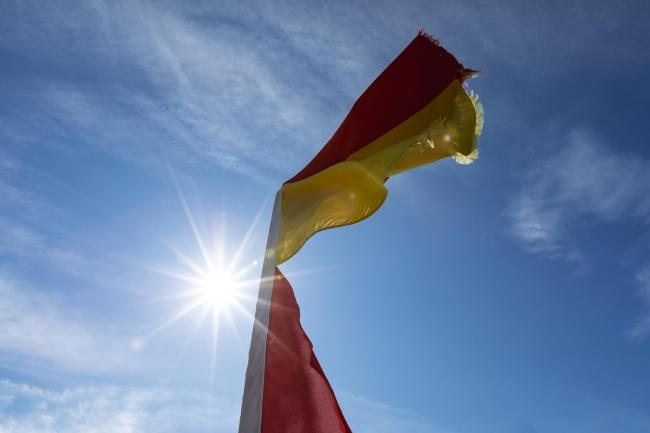 Red and yellow lifeguard flags with a sun flare behind. Credit: 