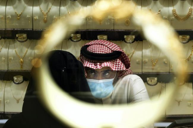 A Saudi vendor is seen through a bracelet as a woman buys jewels (Amir Nabil/AP)