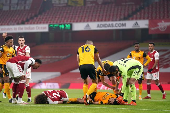 Players reacts after Arsenal's David Luiz (left, floor) clashes heads with Wolves' Raul Jimenez (right, floor)