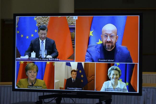 A screen displays Chinese president Xi Jinping, top left, European Council president Charles Michel, top right, European Commission president Ursula von der Leyen, bottom right, French president Emmanuel Macron, bottom centre, and German chancellor Angela