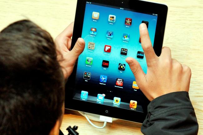 A person using an Apple iPad tablet device.