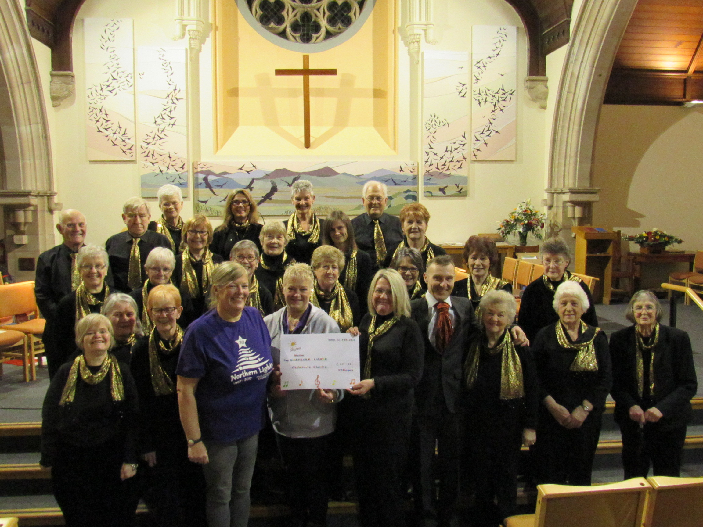 The chairperson of the NE Singers choir, Jennifer Ricketts, presents the cheque to Karen Jones MBE, chair of Northern Lights, and Wendy Reilly, treasurer.
