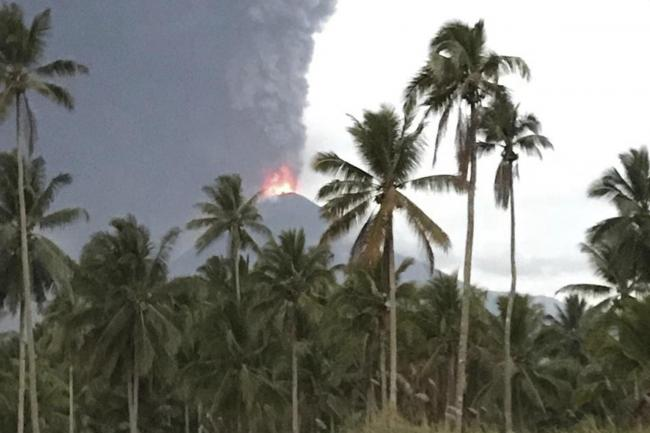 Plumes of volcanic ash rise out of Mount Soputan