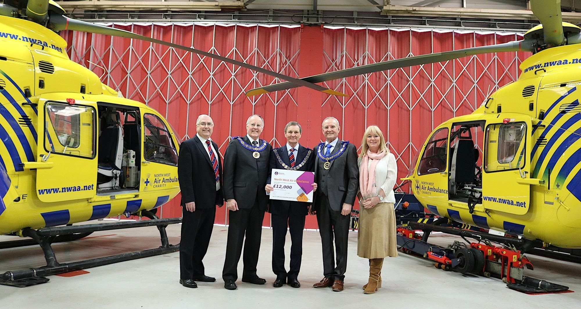 Pictured in the middle of two ambulances and with hard working fund raisers and managers from the NWAAS are Cheshire Freemason Simon Palfreyman, David Walmsley from West Lancashire and John Farrington from East Lancashire.